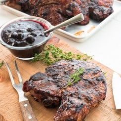A Grilled Pork Chops with Blueberry Balsamic BBQ Sauce on a wooden cutting board