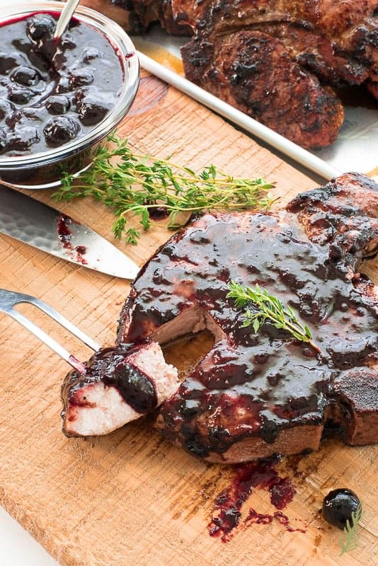 A bite of meat is cut away from an individual grilled pork chop that's been sauced with Blueberry Balsamic BBQ Sauce