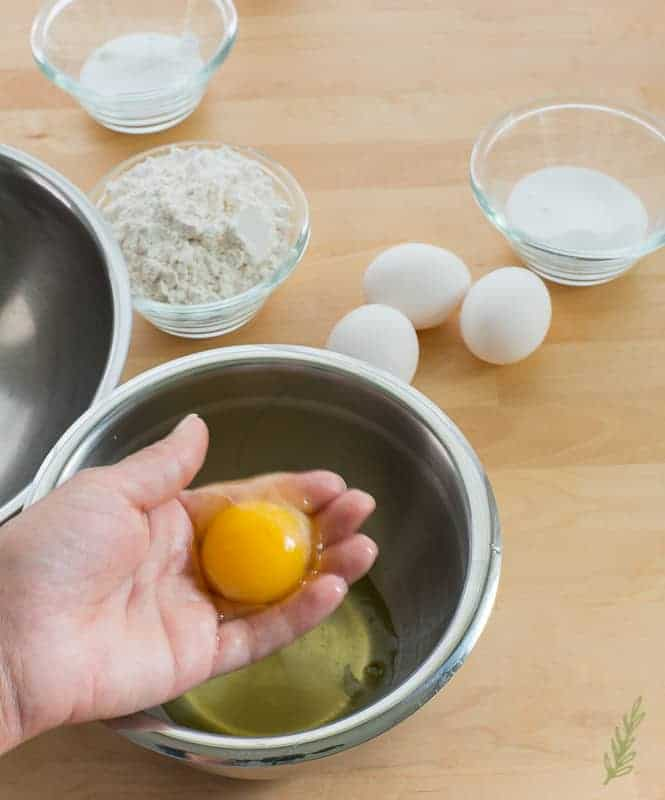 A hand holds an egg yolk after separating it from the yolk over a metal bowl.