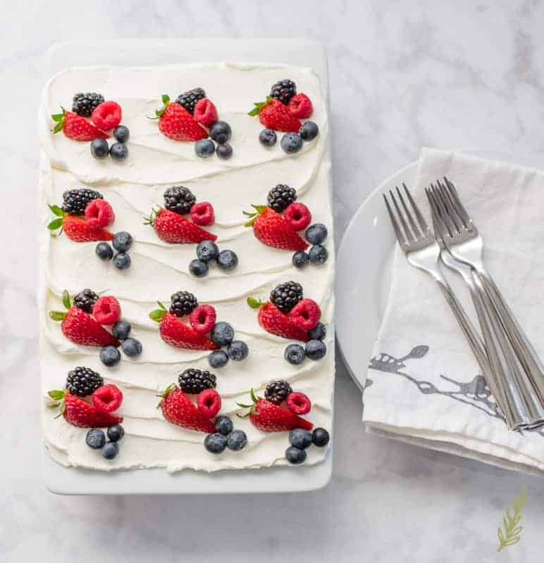 The finished Berry Tiramisu is decorated with fresh berries. It sits next to a stack of white plates and forks.