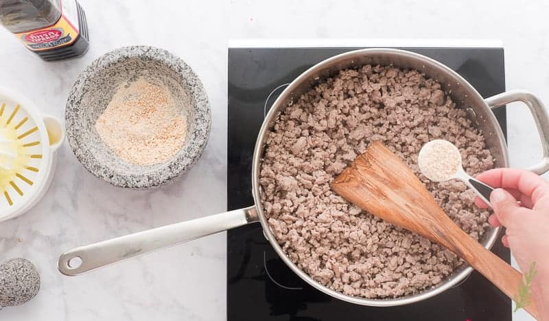 The sticky rice powder is added to the pan with the cooked ground pork. Fish sauce, more rice powder and lime juice are at left