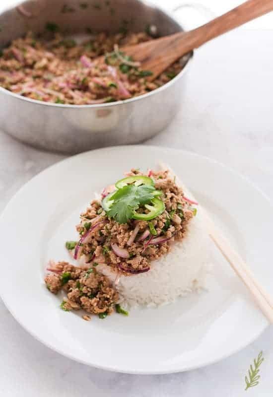 A serving of Larb Moo on a bed of white rice sits on a white plate next to a silver pan that was used to cook the larb.