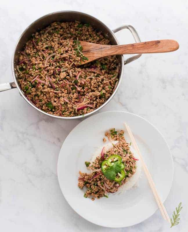 The pan of Larb Moo is at top left. Next to it is a white plate with steamed white rice and a serving of larb moo. Chopsticks rest on the plate