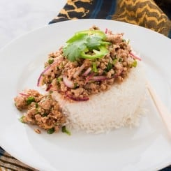 Larb Moo on a bed of steamed white rice on a white plate