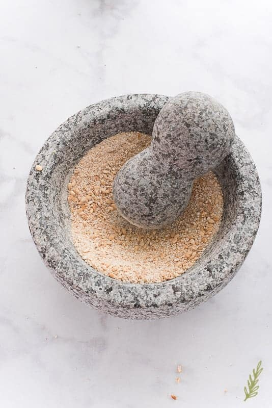 The sticky rice is ground to a powder in a stone mortar and pestle