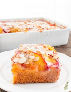 A portion of the Nectarine-Almond Coffee Cake in foreground with a pan of bread in the background