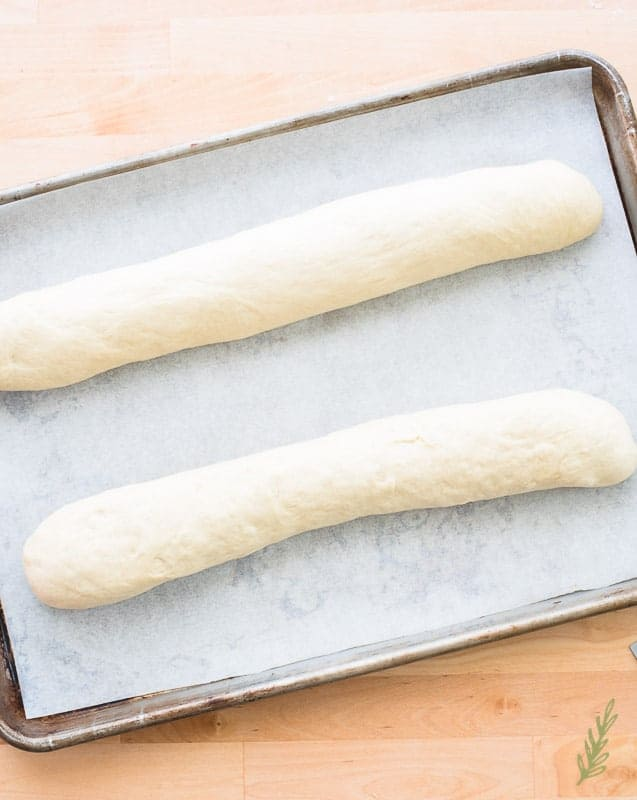 Two rolls of dough sit on a sheet of parchment paper on a half sheet pan