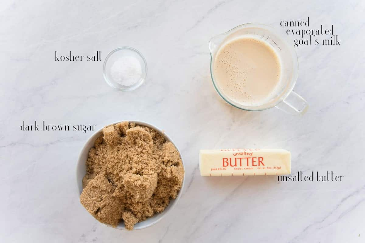 The ingredients to make Cajeta on a white surface: kosher salt, canned evaporated goat's milk, unsalted butter, and brown sugar.