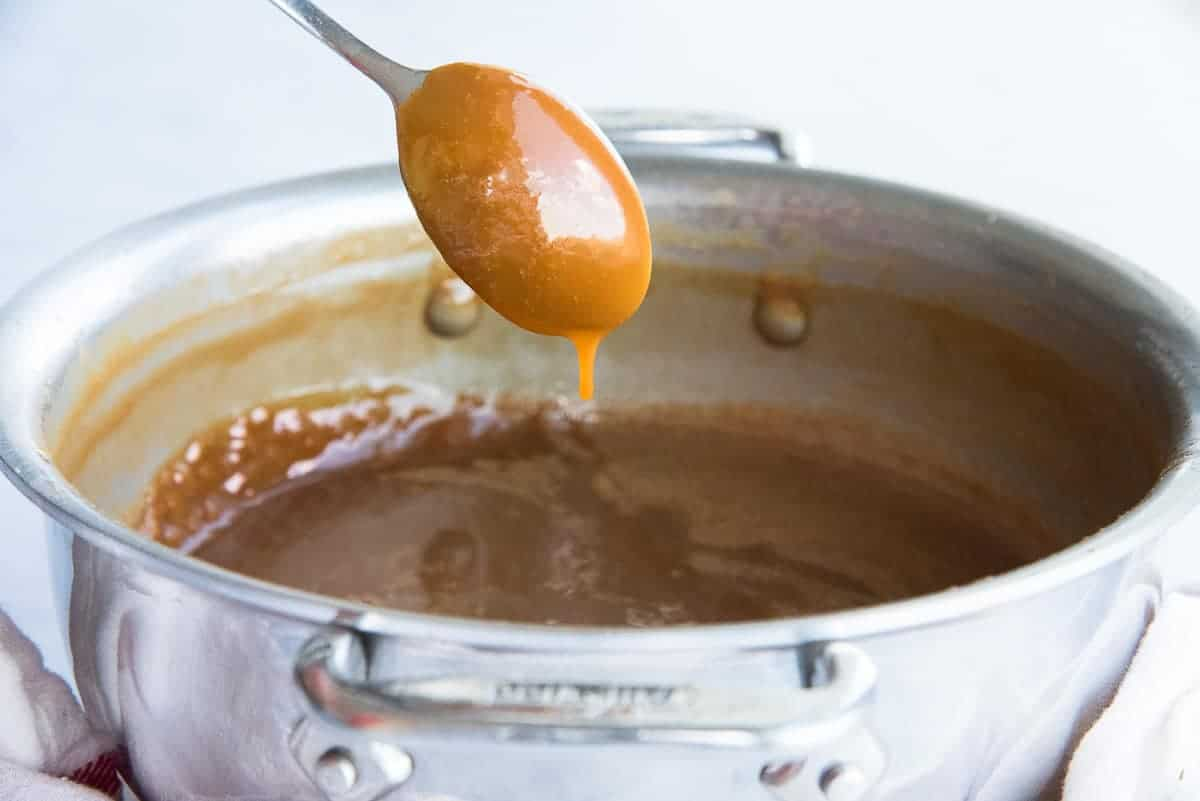 The sauce drips slowly from a spoon after being picked up from the pot.