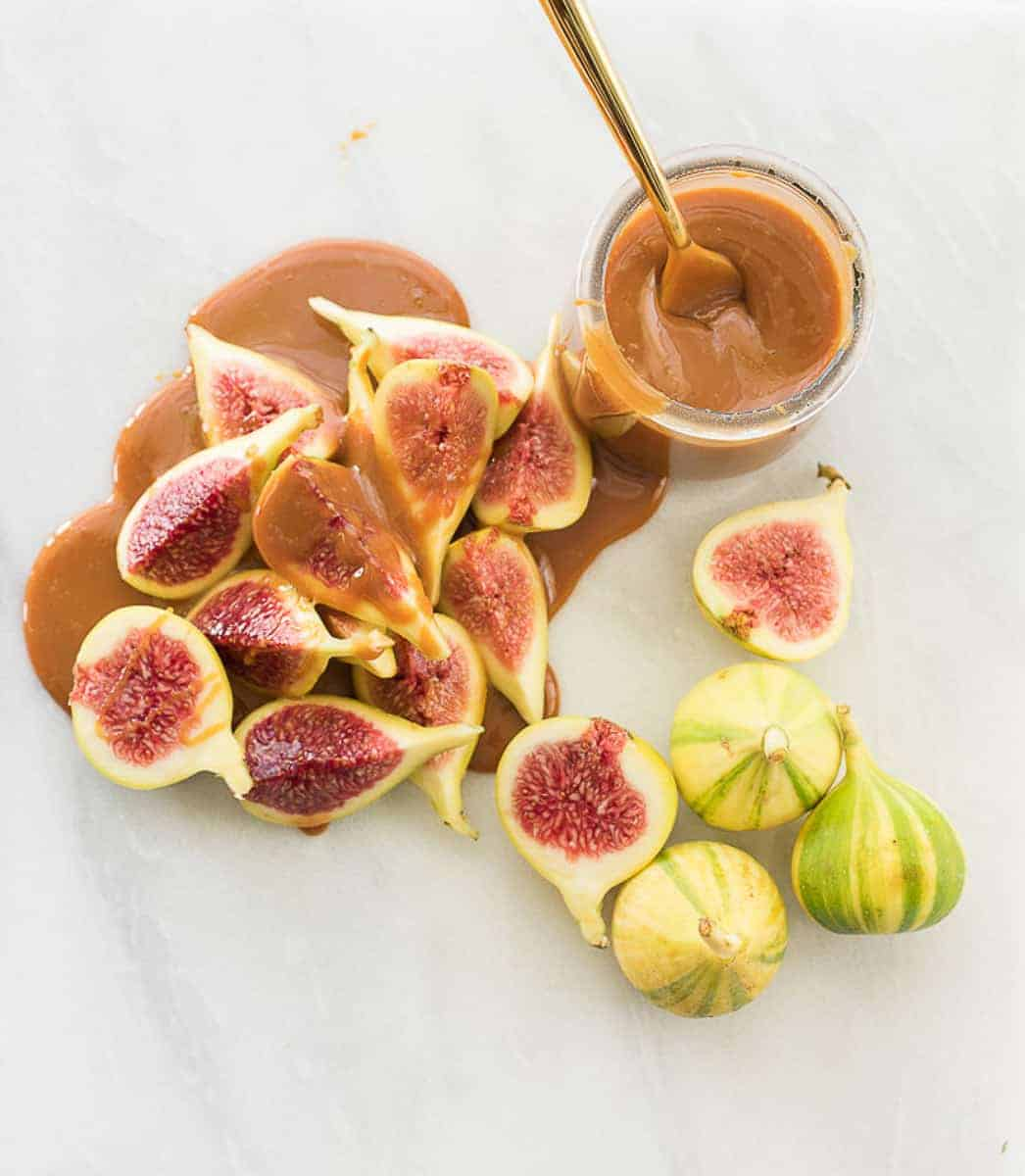 Overhead image of a pile of cut tiger-striped figs covered in cajeta from a nearby glass jar.
