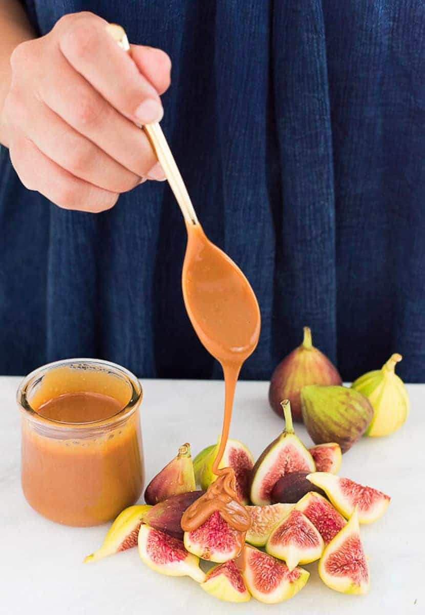 A person drizzles Cajeta from a gold spoon onto a pile of fresh, cut figs which are next to a small jar of cajeta