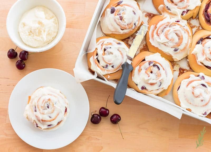 A glazed sweet roll sits next to a panful of Cherry Sweet Rolls with Cream Cheese Icing