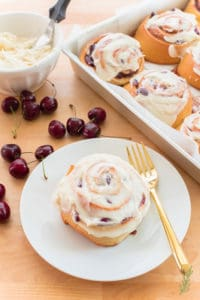 Cherry Sweet Roll with Cream Cheese Icing on a white plate with a gold fork