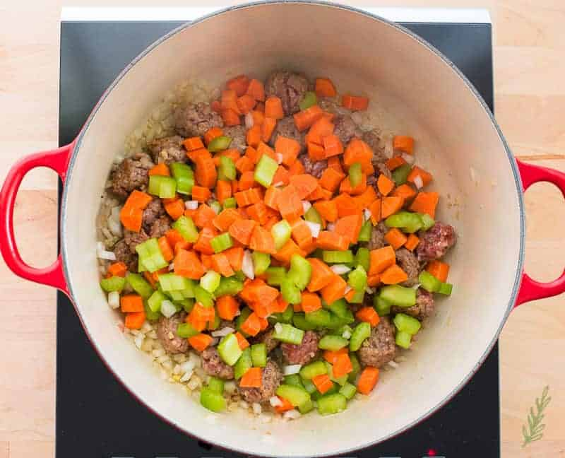 Carrots and celery are added to the pot with the browned sausage, onions, and garlic.