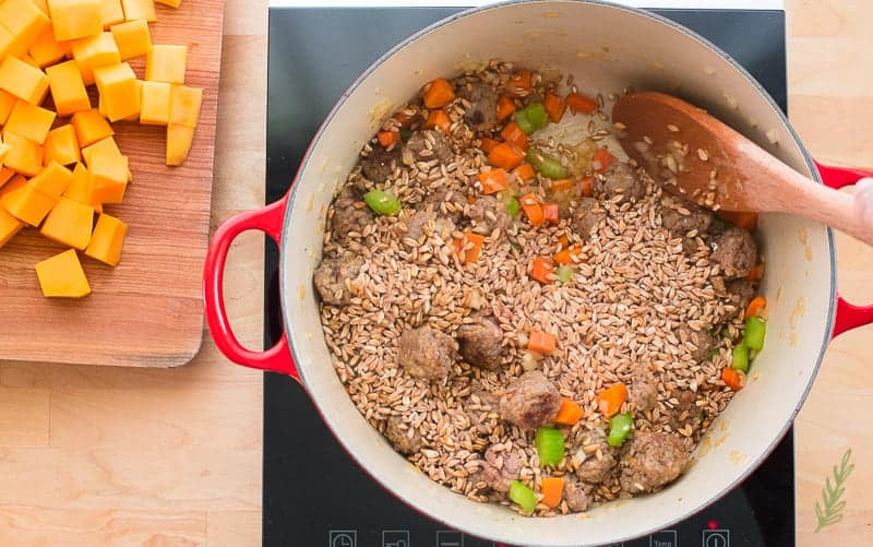 Farro is stirred into the soup pot with the meatballs and veggies using a wooden spoon.