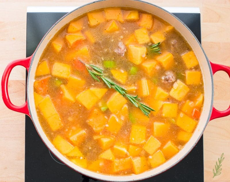 Rosemary, butternut squash and chicken stock are added to the pot with the veggies