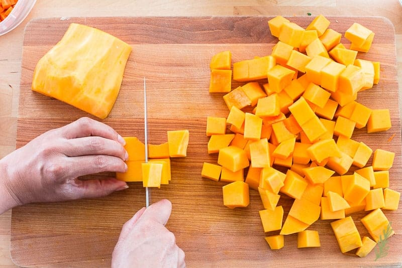 A hand cuts the butternut squash into chunks on a wooden cutting board