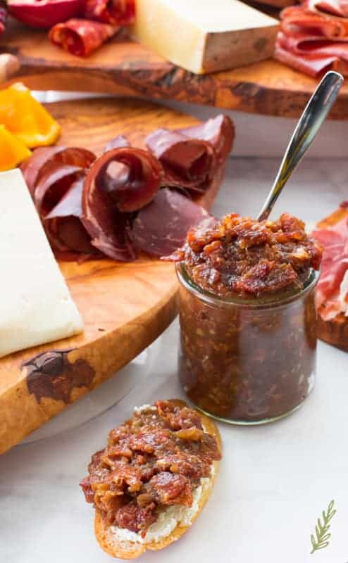 A side view of a small jar of Bacon Bourbon Jam with charcuterie in the background