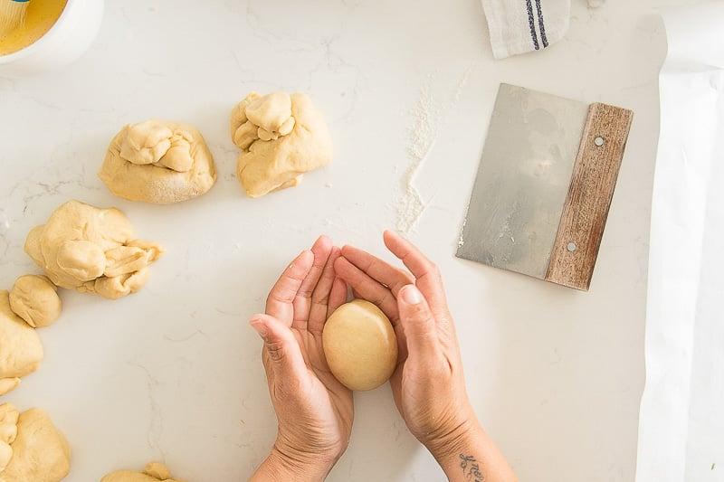 Hands forming brioche dough into balls