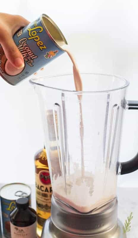 A hand pours coconut milk from a can into a blender