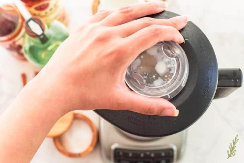 A hand places a black lid onto a blender.
