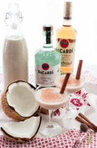 Two coupe glasses of Coquito next to a cracked coconut and in front of bottles of rum and coquito