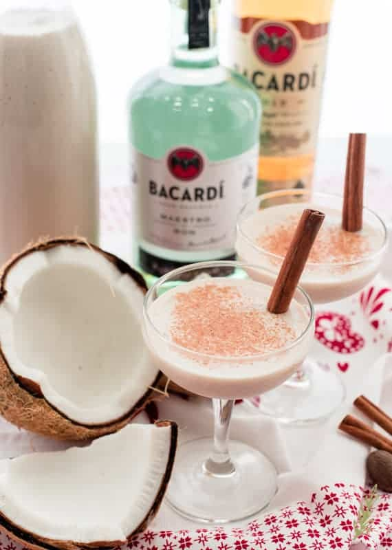 two coupe glasses filled with Coquito garnished with cinnamon sticks in front of rum bottles next to a cracked coconut on a white and red towel