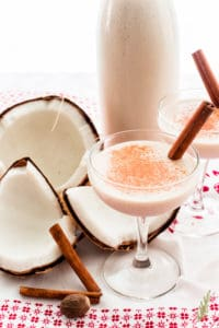 Two coupe glasses filled with coquito on a white and red towel in front of a bottle of coquito and beside a cracked coconut and whole spices.