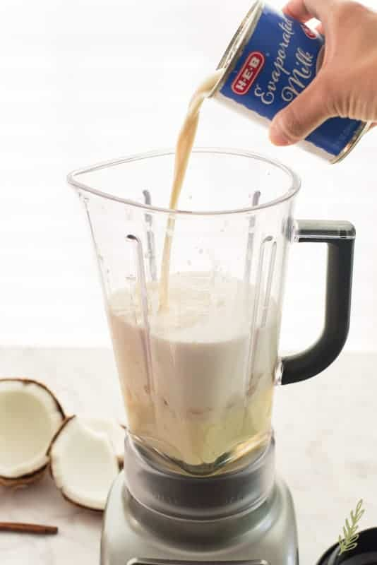 A hand pours evaporated milk from a can into a blender