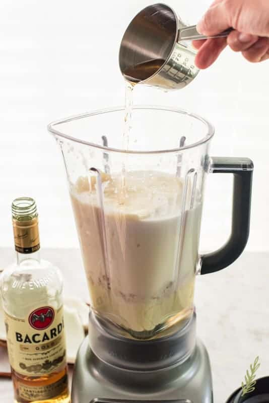 Rum is added to a blender filled with milks
