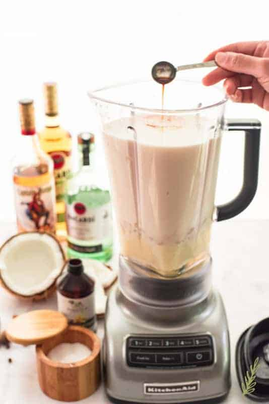 A hand pours a teaspoon of vanilla into a blender filled with other Coquito ingredients