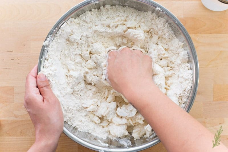 Hands cut the butter and shortening into the flour in a silver bowl