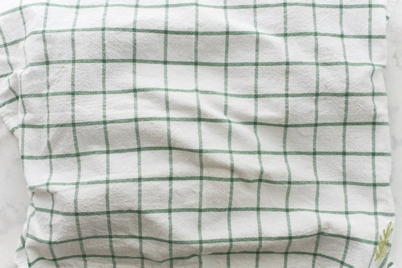 A green and white plaid towel is placed over the baked potatoes to steam and loosen the jackets