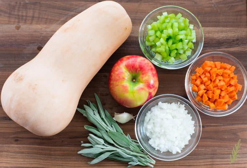 Ingredients to make Butternut-Apple Bisque on a wooden surface: squash, apple, celery, carrot, onion. sage, and garlic.