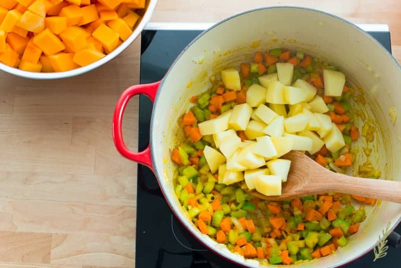 Diced Apple is added to the dutch oven with the onions, celery and carrots.