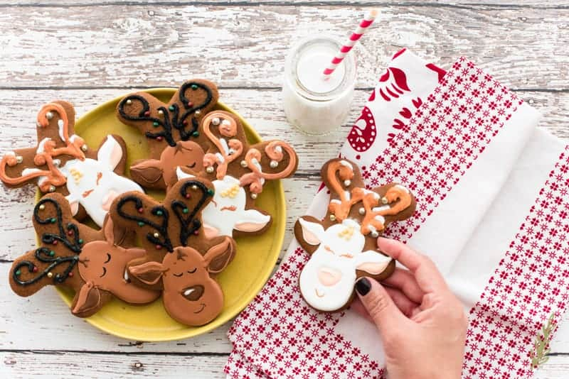 A hand picks up a Gingerbread Reindeer Cookie from a pile of them on a yellow plate.