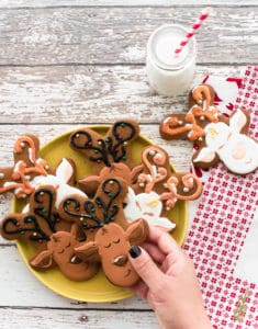 A hand holds a Gingerbread Reindeer above a yellow plate filled with more cookies. A glass jar of milk has a red and white straw in it.