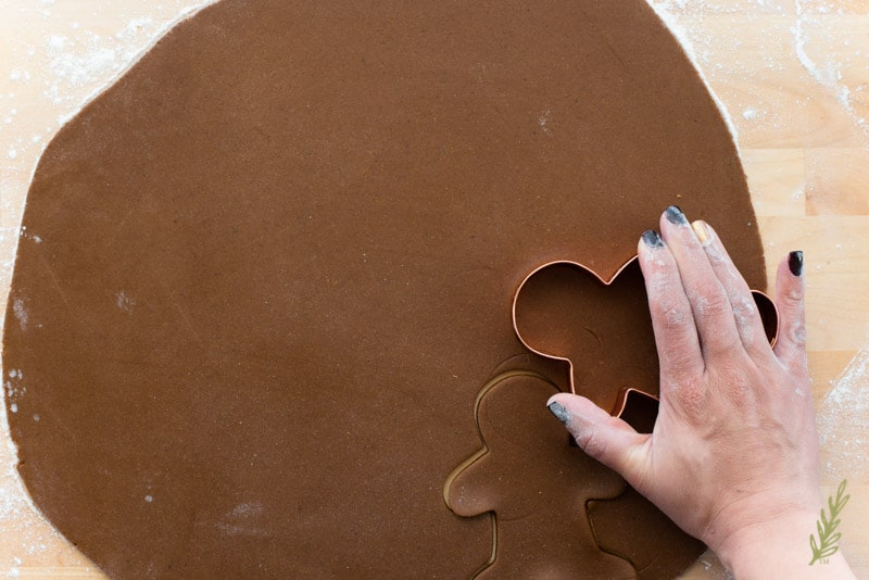 A hand uses a Gingerbread man cookie cutter to cut out the Reindeer
