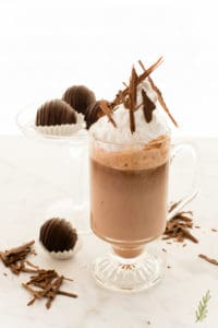 A glass of Original Truffle Hot Chocolate surrounded by other truffles and shaved chocolate