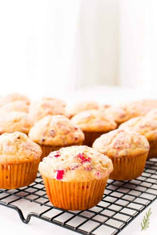 A Vanilla-Cranberry Muffin sits with others on a black cooling rack