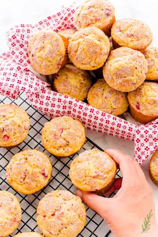 a basket filled with Vanilla-Cranberry Muffins sites next to a cooling rack with more muffins