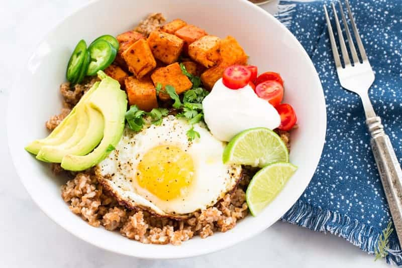 The cilantro-lime bulgur bowls are tops with garnishes in a white bowl next to a blue napkin with a silver fork on top