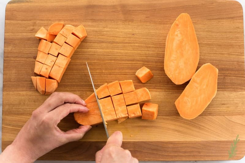 The sweet potatoes are cut into chunks on a wooden cutting board