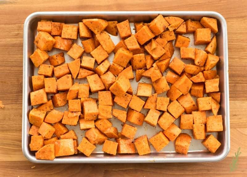 The seasoned sweet potatoes on a silver sheetpan
