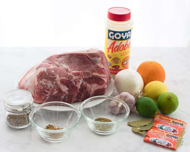 The ingredients for Slow Cooker Pulled Pork in Mojo Sauce: pork shoulder, spices, sazón, bay leaves, citrus, onions, garlic, and adobo