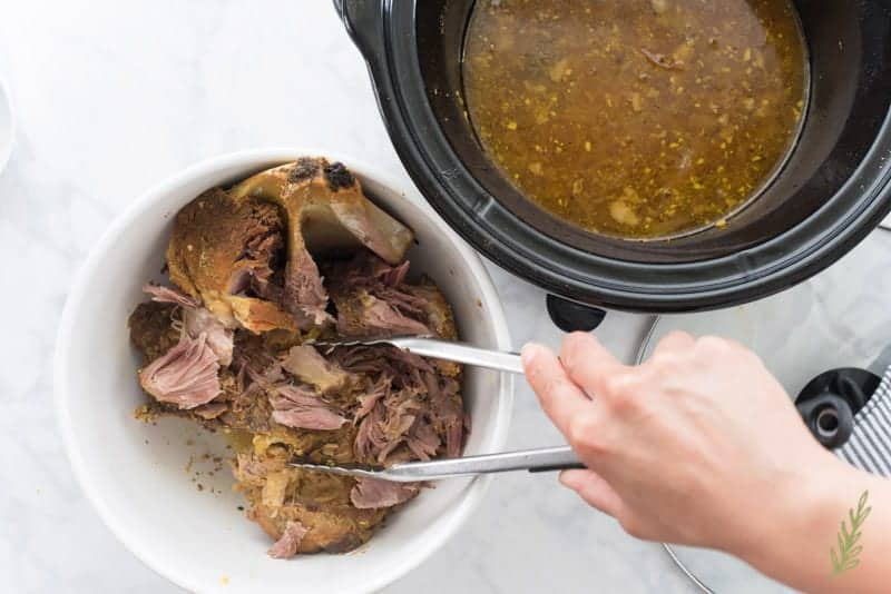 The pork is pulled from the slow cooker and place in a bowl with a pair of tongs