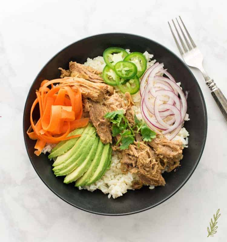 Slow Cooker Pulled Pork in Mojo Sauce is served on a bed of rice with thinly sliced veggies in a black bowl. A silver fork sits to the top right of the bowl.