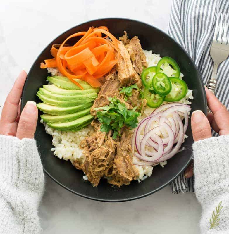 The Slow Cooker Pulled Pork in Mojo Sauce is in a black bowl on a bed of white rice. Thinly sliced red onions, avocados, and jalapenos, and shaved carrots surround the pork.