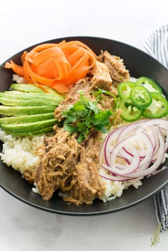 A close up shot of a bowl of Slow Cooker Pulled Pork in Mojo Sauce with thinly sliced veggies surrounding it on a bed white rice.