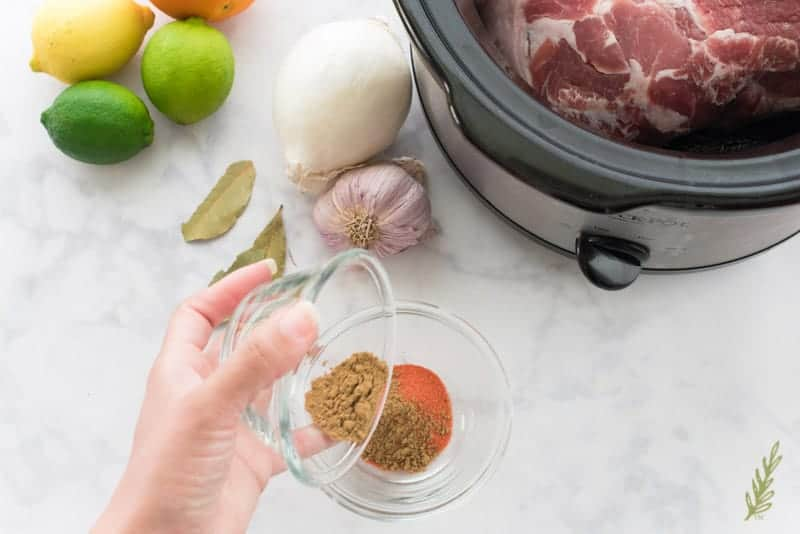 A hand adds the bowlful of cumin to the spice blend already made in a separate bowl. Citrus fruits, onion, garlic, and bay leaves sits to the left of the Slow Cooker which has a piece of Pork in it